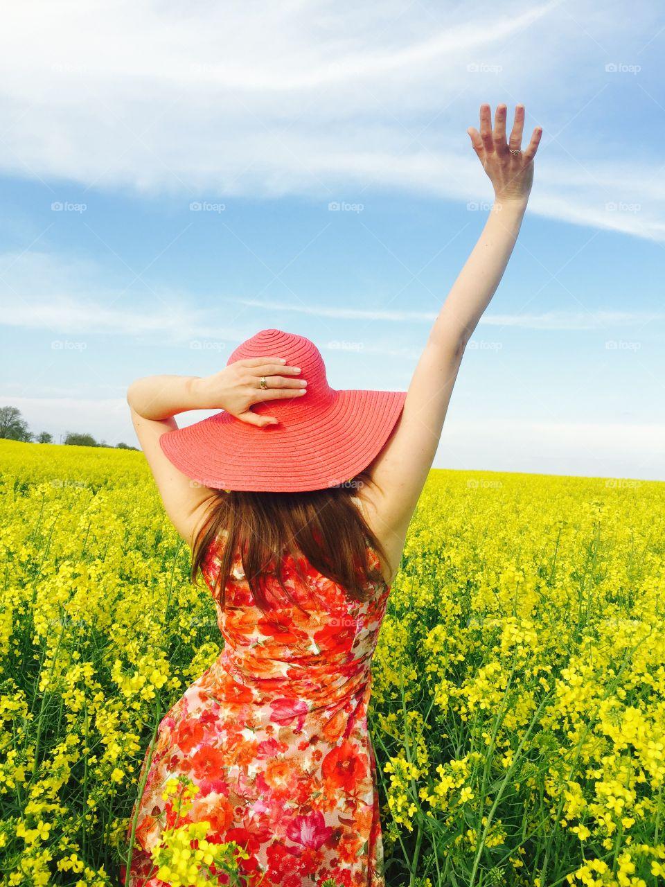 Rear view of girl standing in flower field