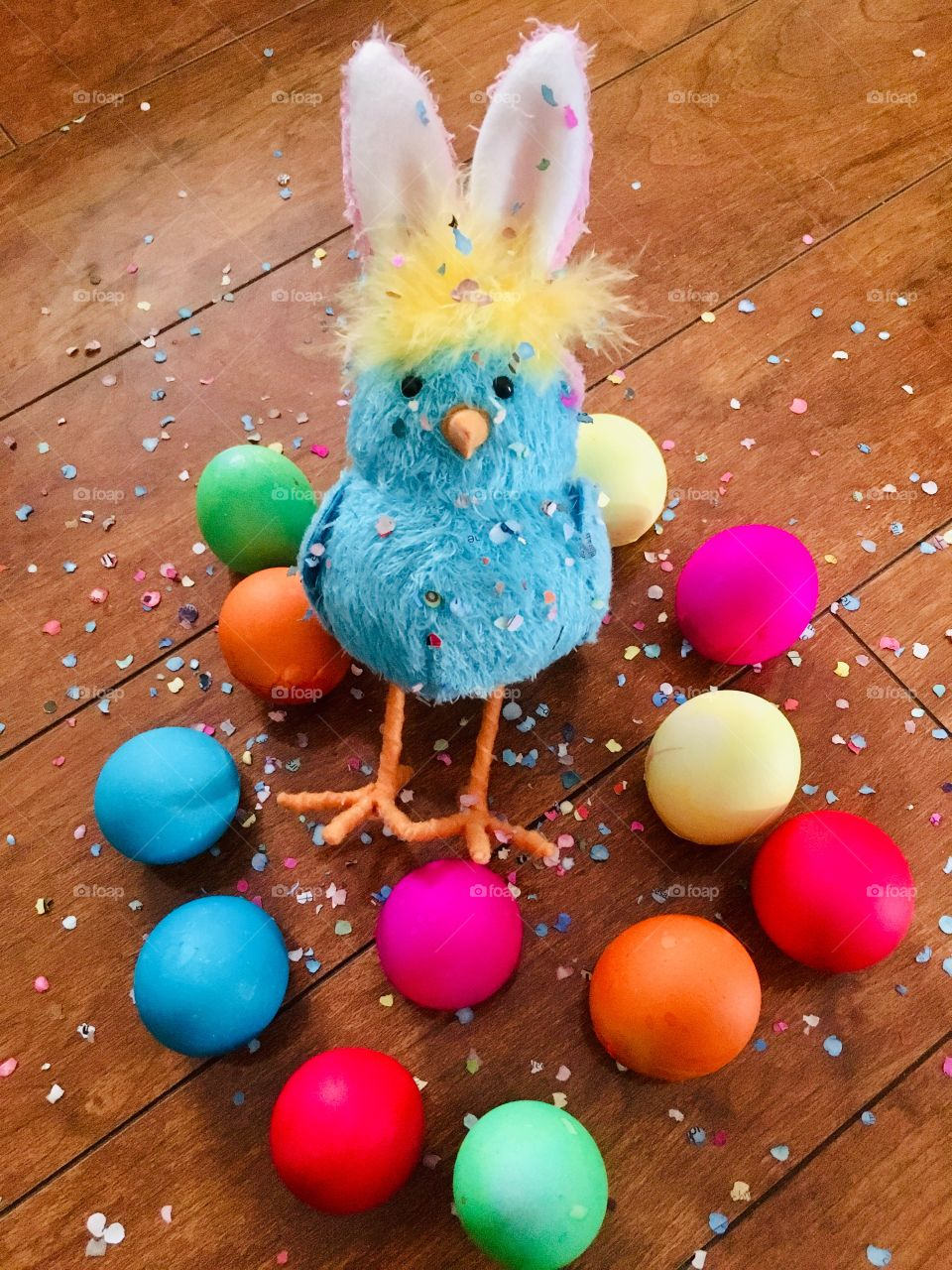 Bunny chick with colorful Easter eggs and confetti