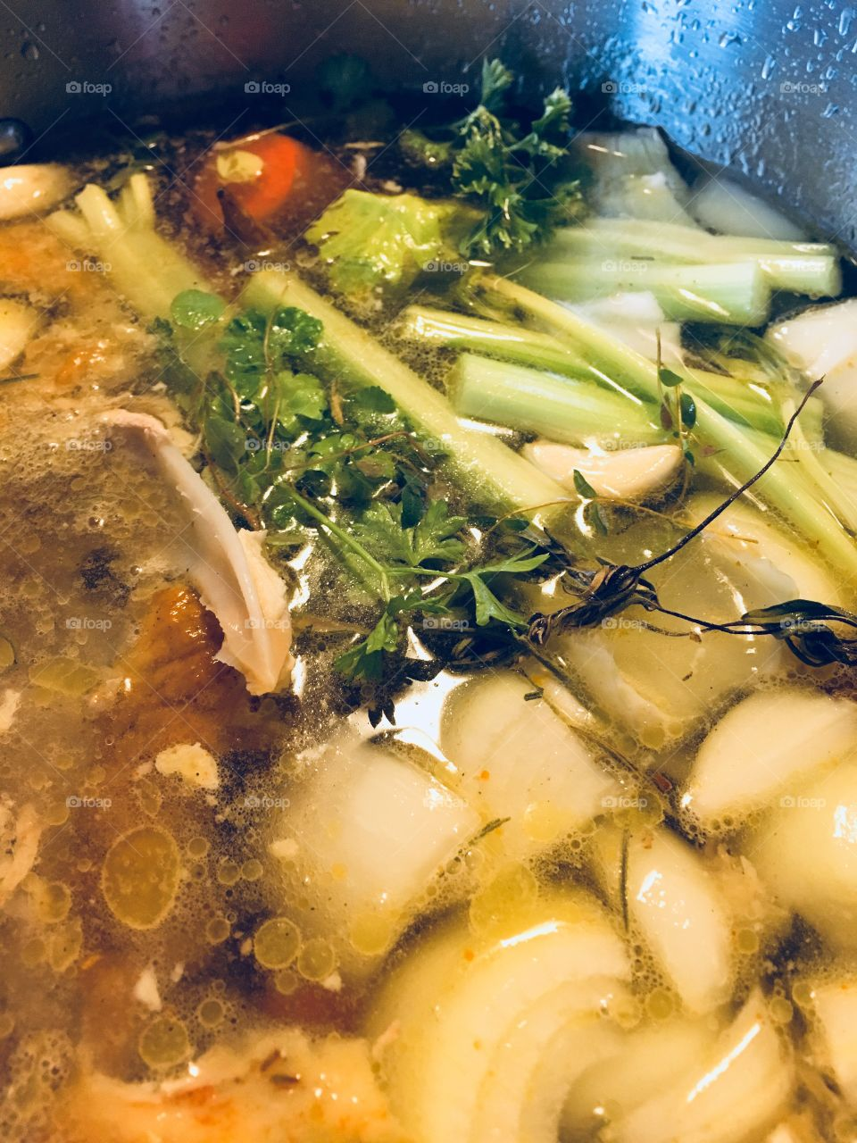 Healing, nutritious chicken bone broth. Soup pot filled with vegetables and herbs.