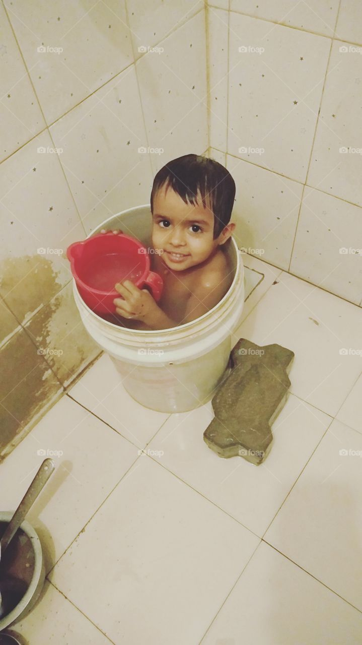 This baby is taking a bucket, So Cute Baby, Beautiful baby, The baby is taking bath in the bathroom, This Girl in the bucket, Enjoy in Summer Time, Nice Baby,