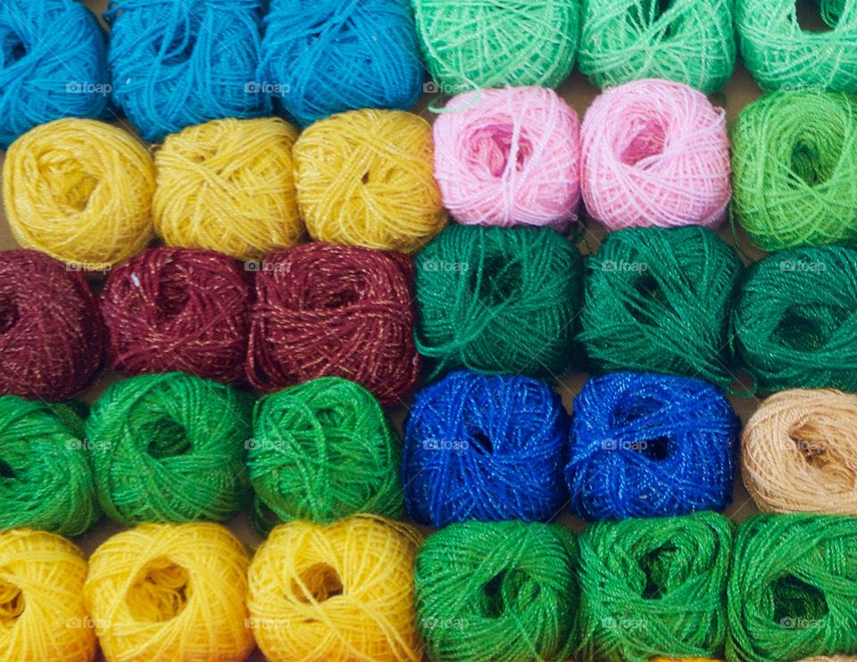 Many multicolored balls of yarn displayed in an upright box for sale on the street in San Miguel de Allende, Mexico.