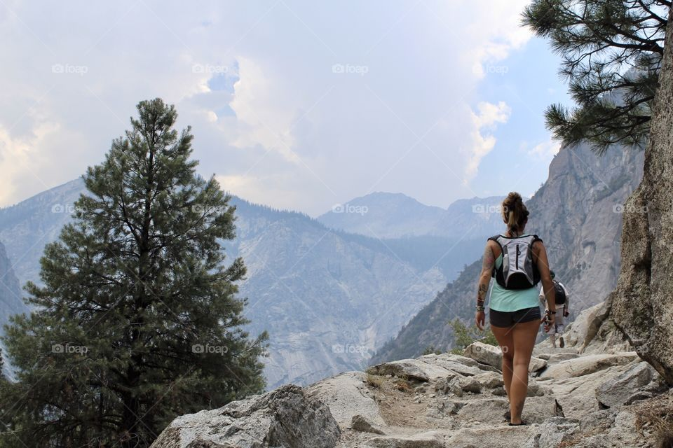 Hiking in national park, girl hiking, uphill, trees and mountains