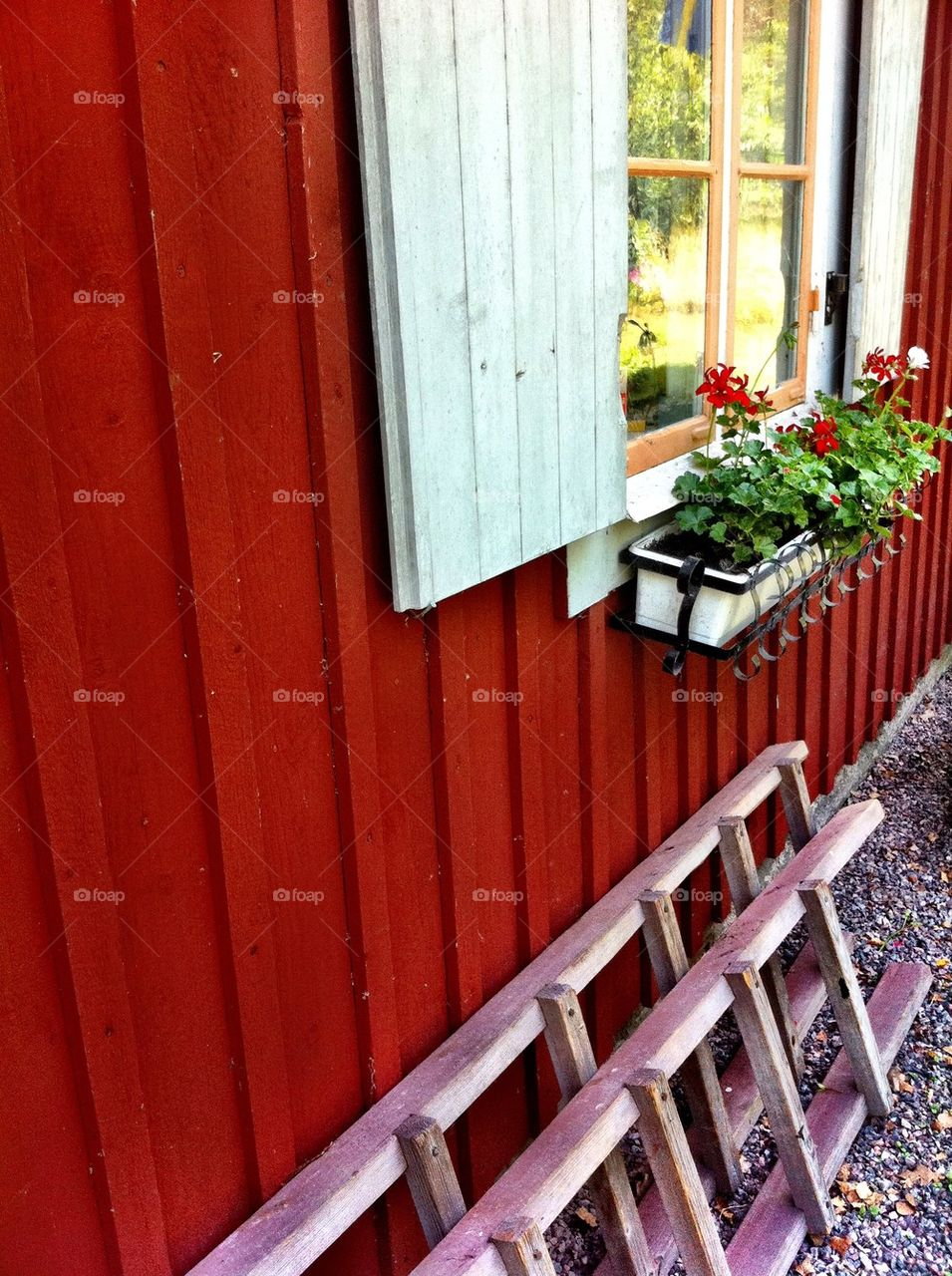 Red wooden house with shutters and flower box.