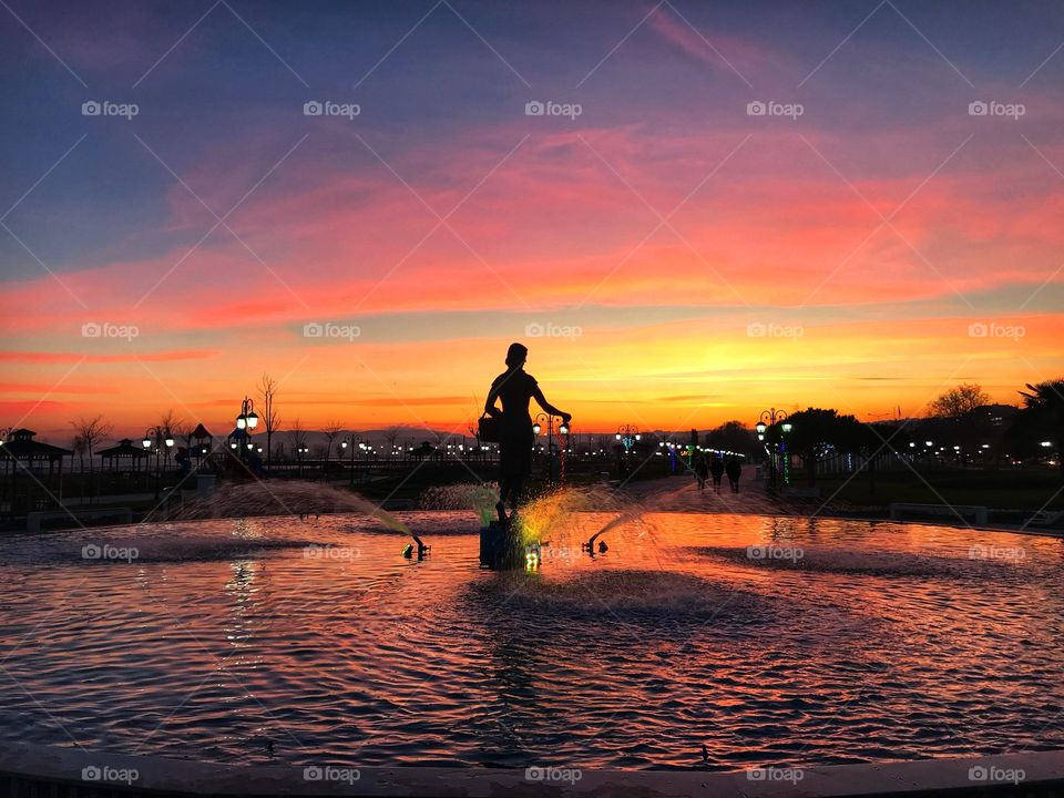 sunset with a woman statue