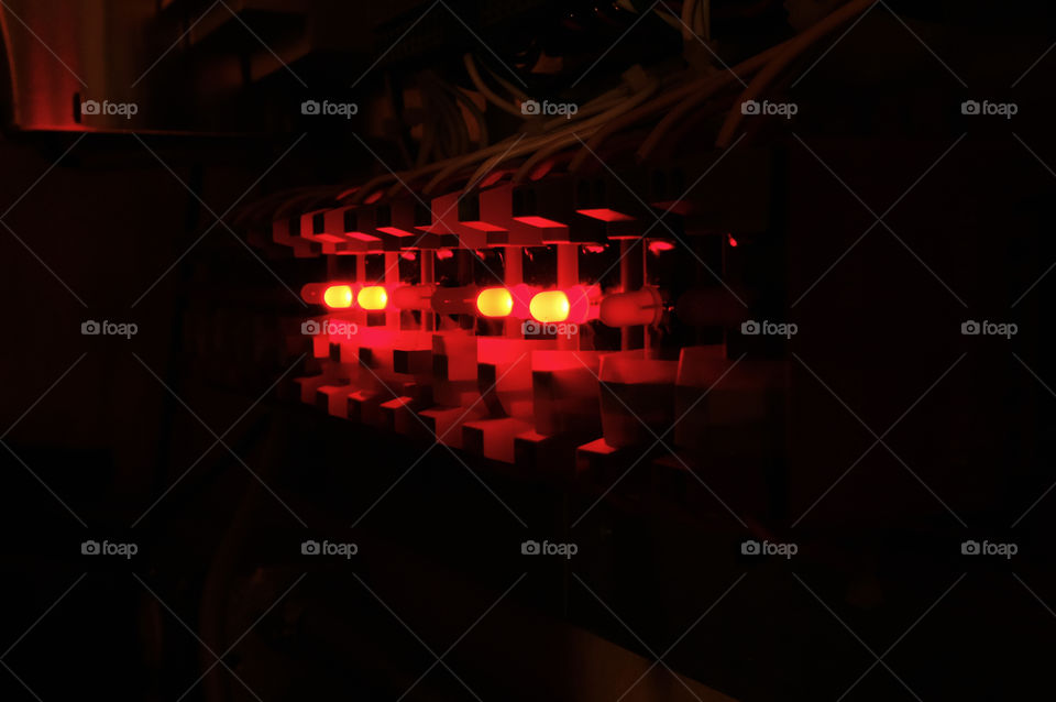 View in the dark of a row of solid state relays with red LED lights used for data acquisition and control systems.