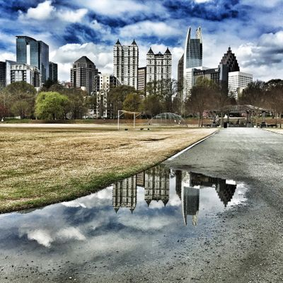 Reflection of skyline in puddle at park