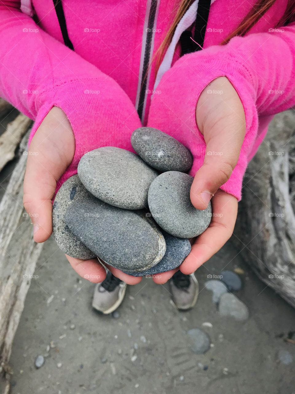 Smooth gray rocks in hands of girl wearing beautiful bright pink sweatshirt and perfect tennis for beach combing!