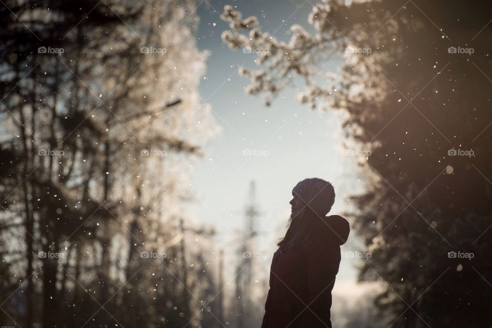 Girl watching snow falling from the trees at sunset, Estonia