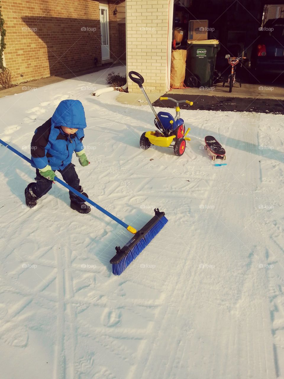small boy sweeping snow in driveway with broom