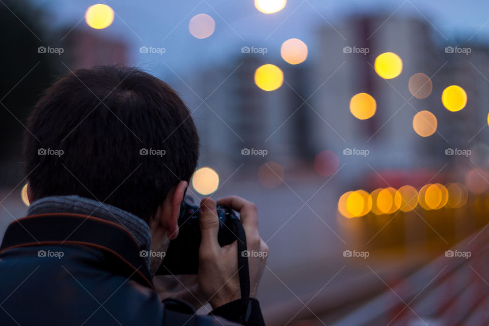 Rear view of a man taking pictures on camera