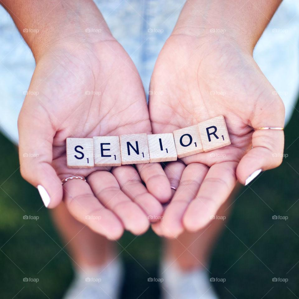 Senior. Hands holding scrabble tiles that spell out senior