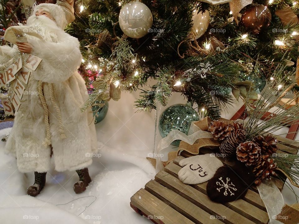 """A white clad traditional Santa Claus holding a """"Merry Christmas"""" sign at the base of a lighted Christmas tree."""
