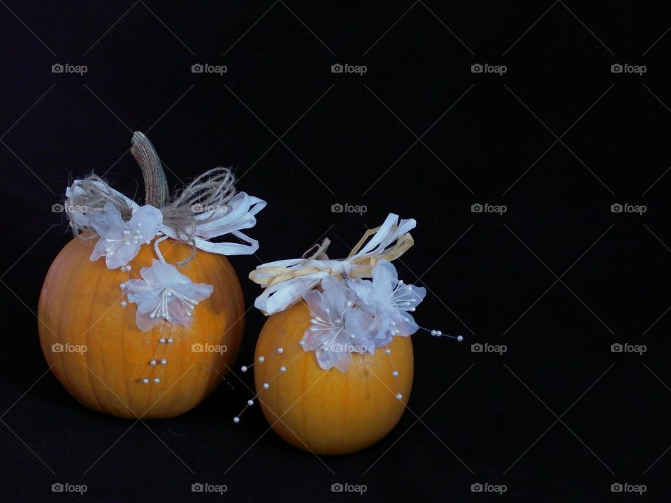Two country style hand decorated pumpkins with beautiful white flowers and beads and brown and white paper lace against a black background with ample copy space.