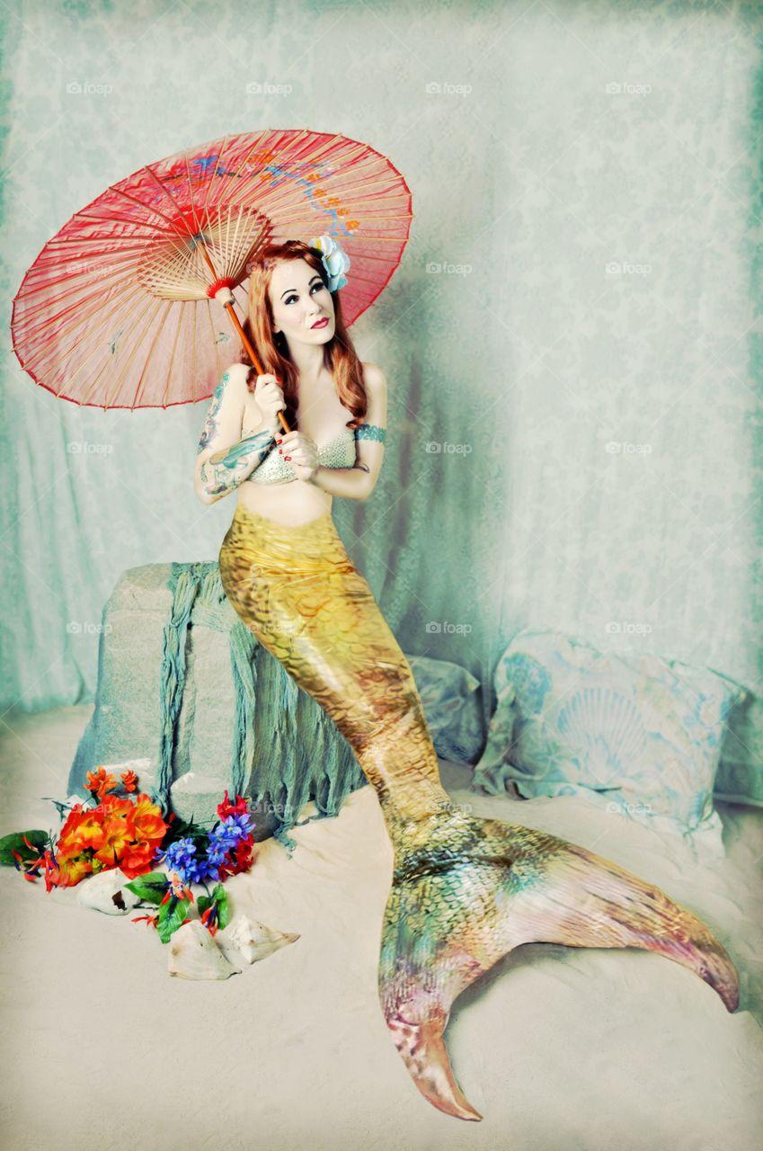 Mermaid sitting on rock holding umbrella
