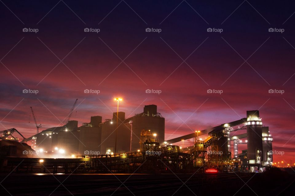 Early morning sunset over an industrial plant. Busy industrial landscape at night with colour in the sky.