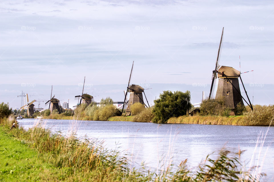 Row of old windmills near the river bank