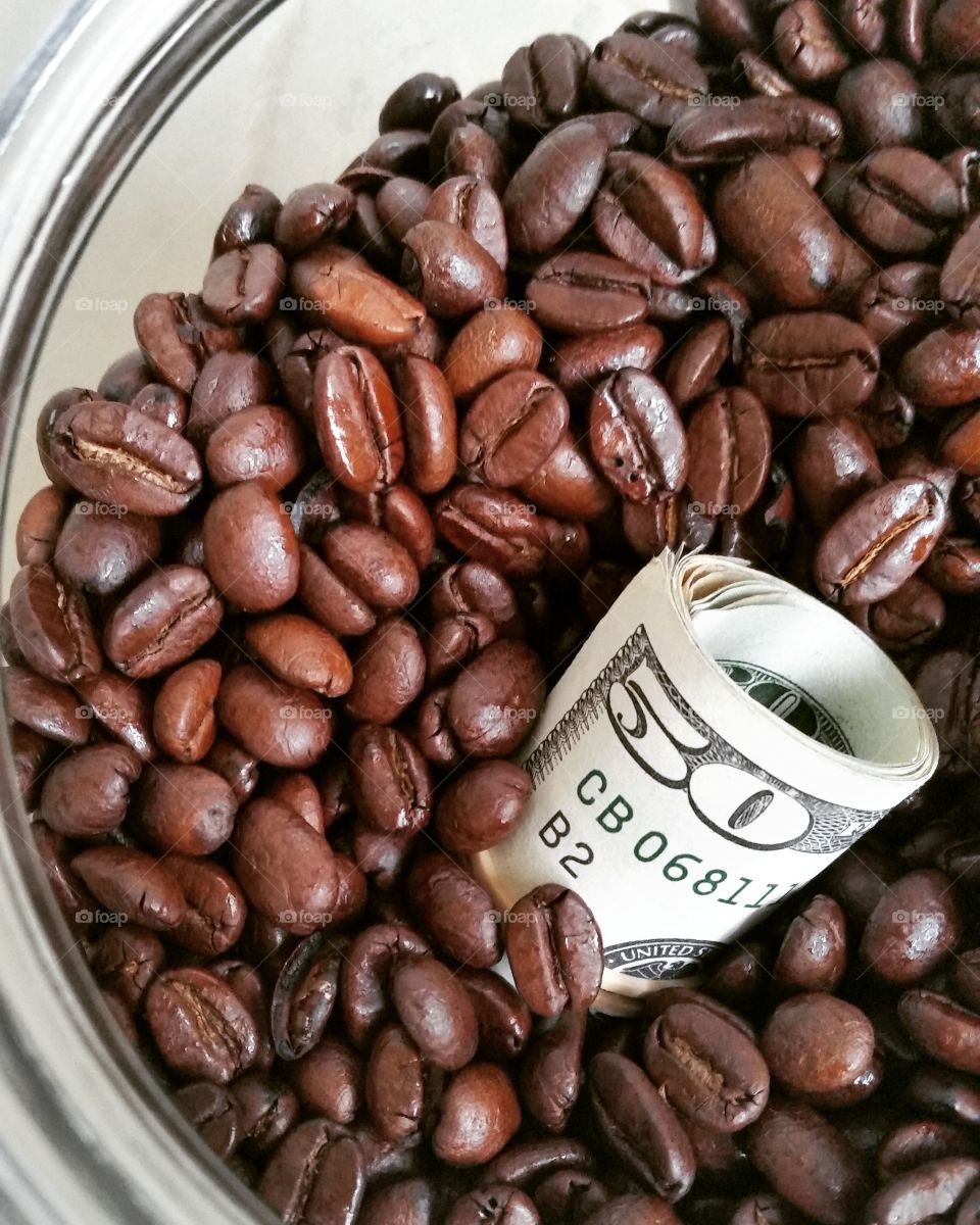 Bowl of roasted coffee beans with american dollar