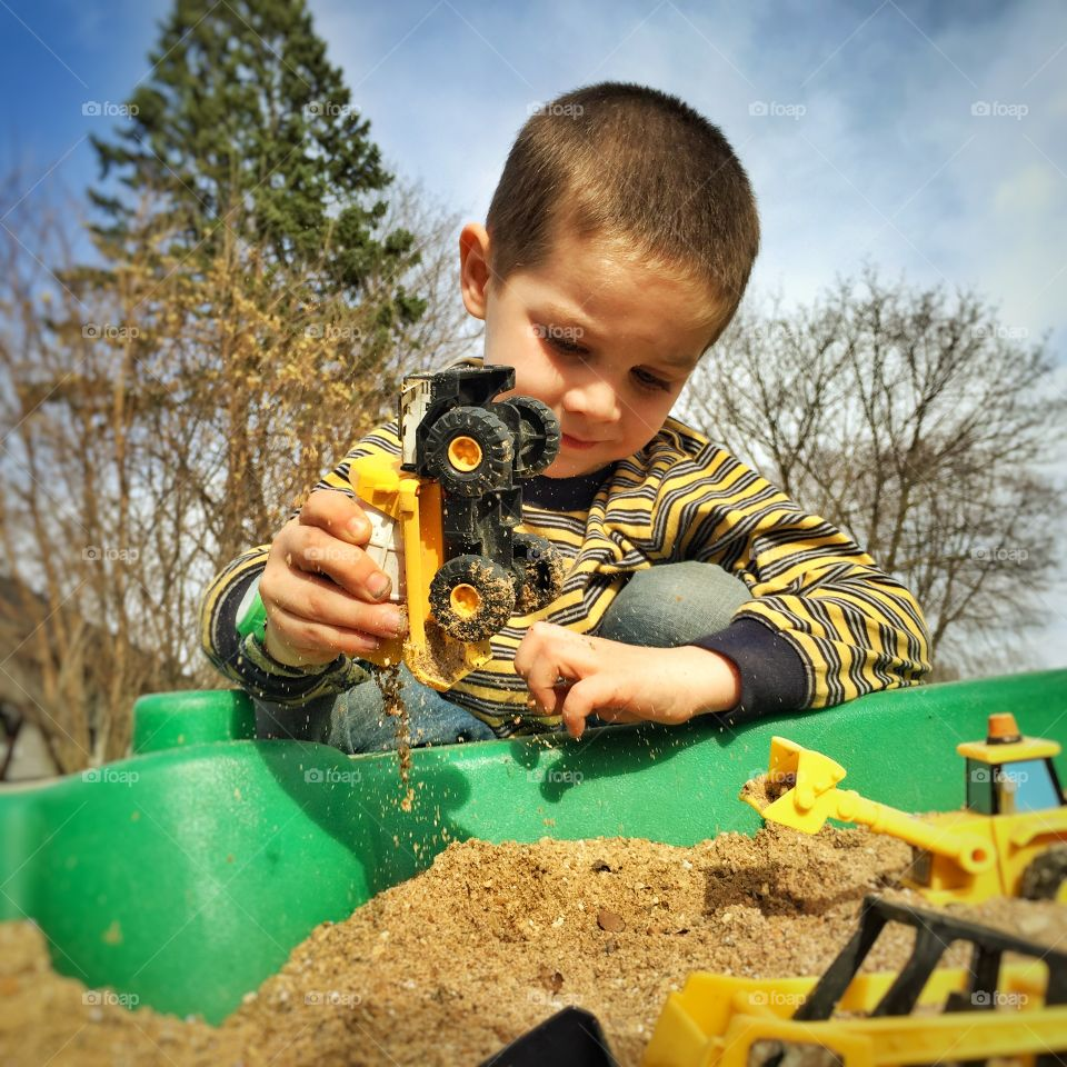 Boy playing with toy vehicles
