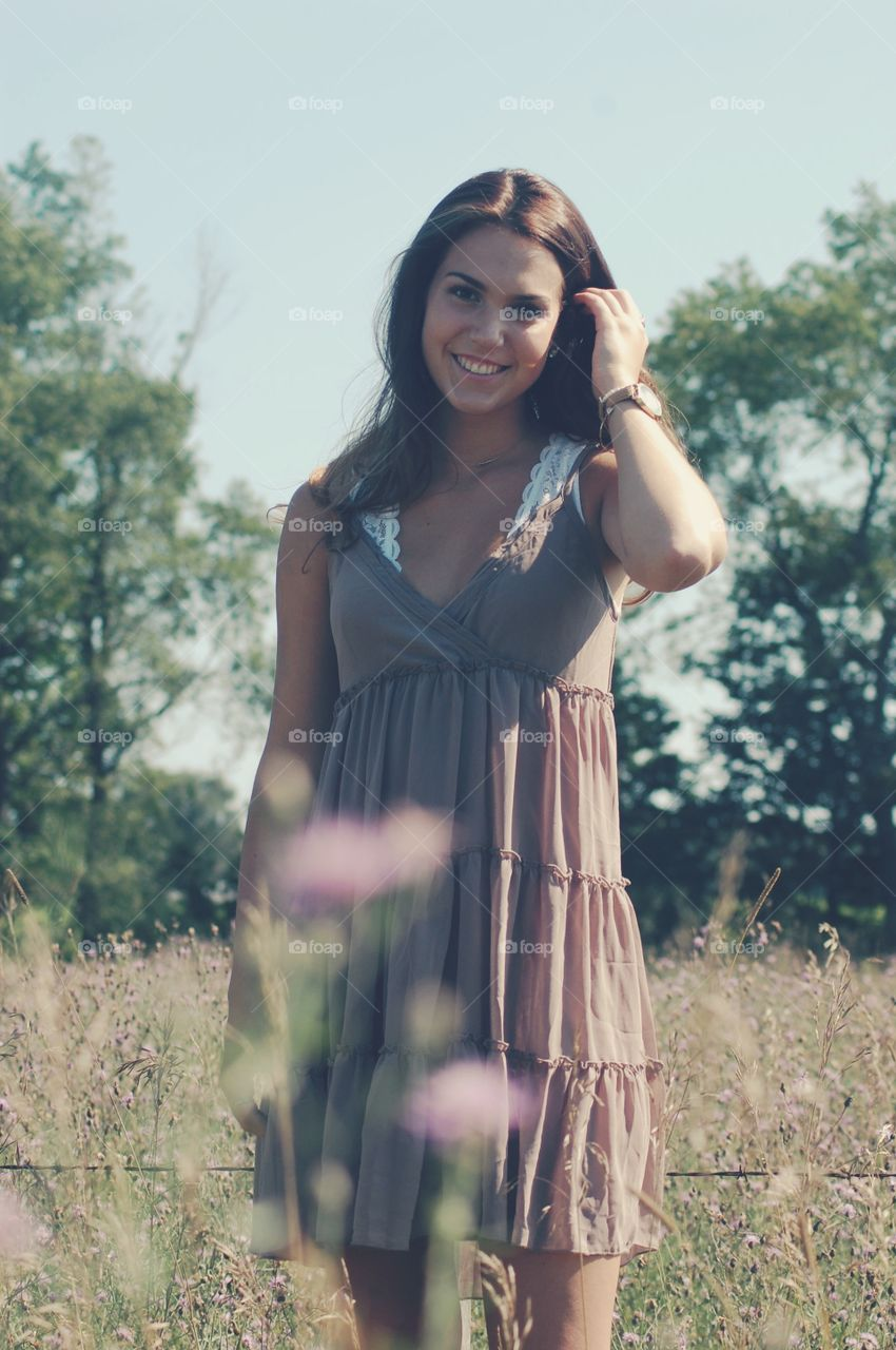 Beautiful smiling woman standing on meadow