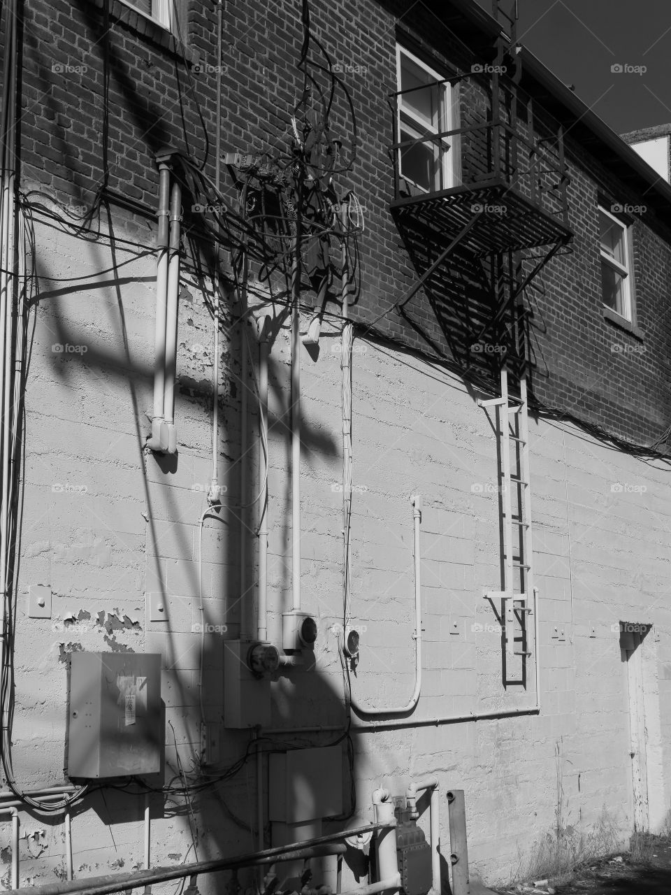 The side of an old concrete building in a city with windows and a fire escape ladder on a sunny summer day.