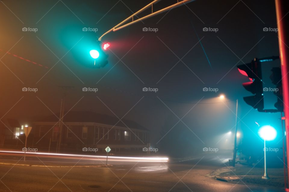 A long exposure of the traffic lights at the corner of my street in the fog.