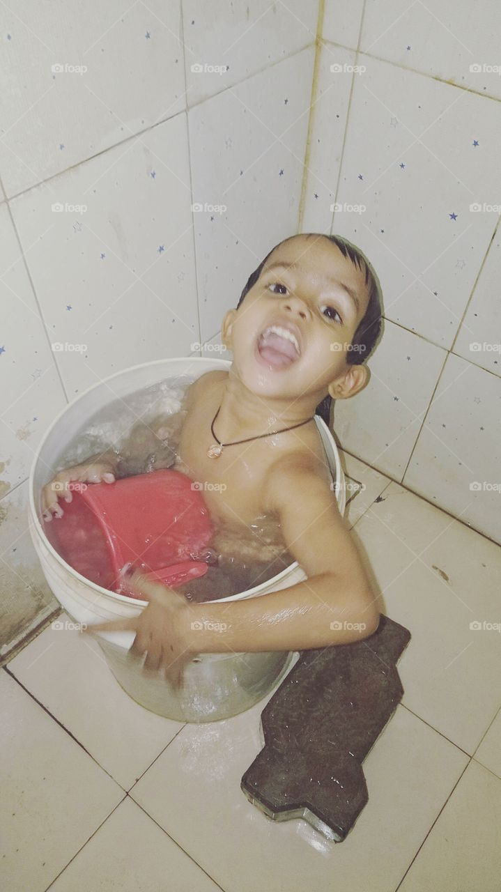 This baby is taking a bucket, So Cute Baby, Beautiful baby, The baby is taking bath in the bathroom, This Girl in the bucket, Enjoy in Summer Time, Nice