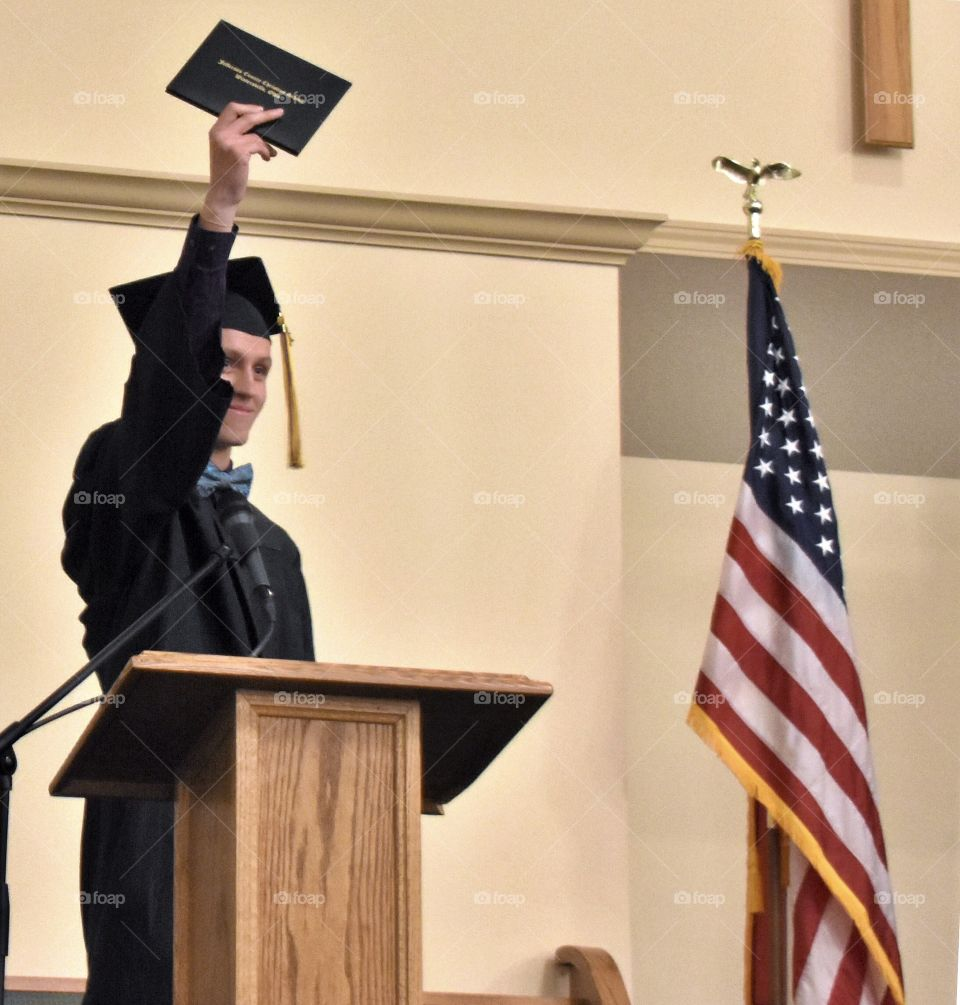 Graduate holding up his diploma, flag in the background