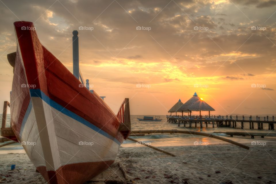 Cambodian Orange beach sunset . Orange sunset at the beach next to the sea. Fishing boat on the shore. Couple straw huts on pier. One fishing boat