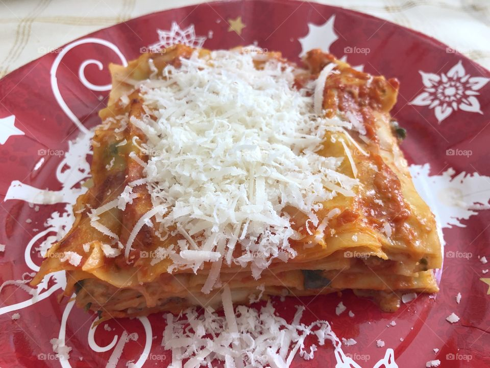Christmas meal in Italy, a dish of lasagne with much grated cheese