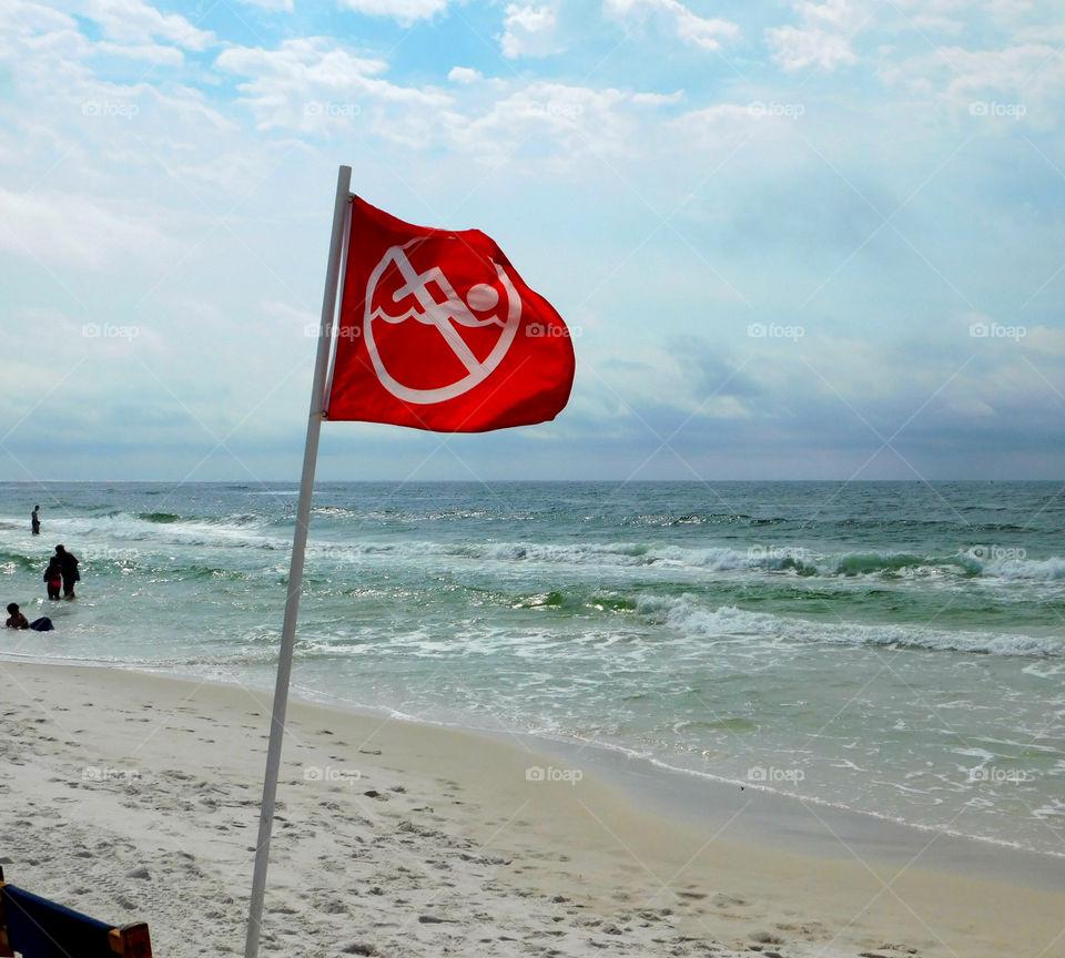 No swimming warning sign on flag at beach