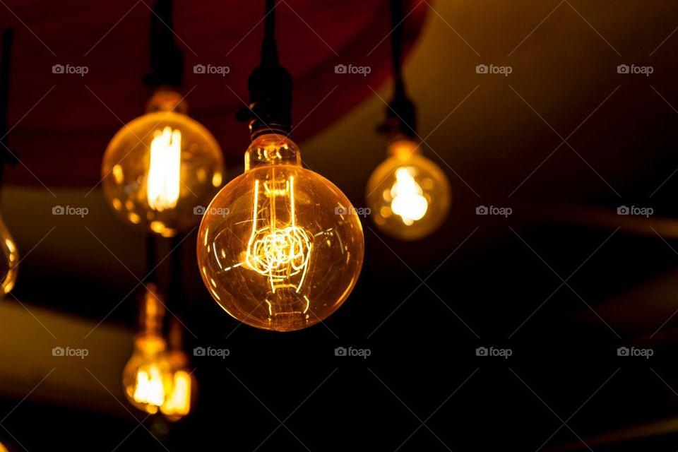 Glowing tungsten light bulbs on black background