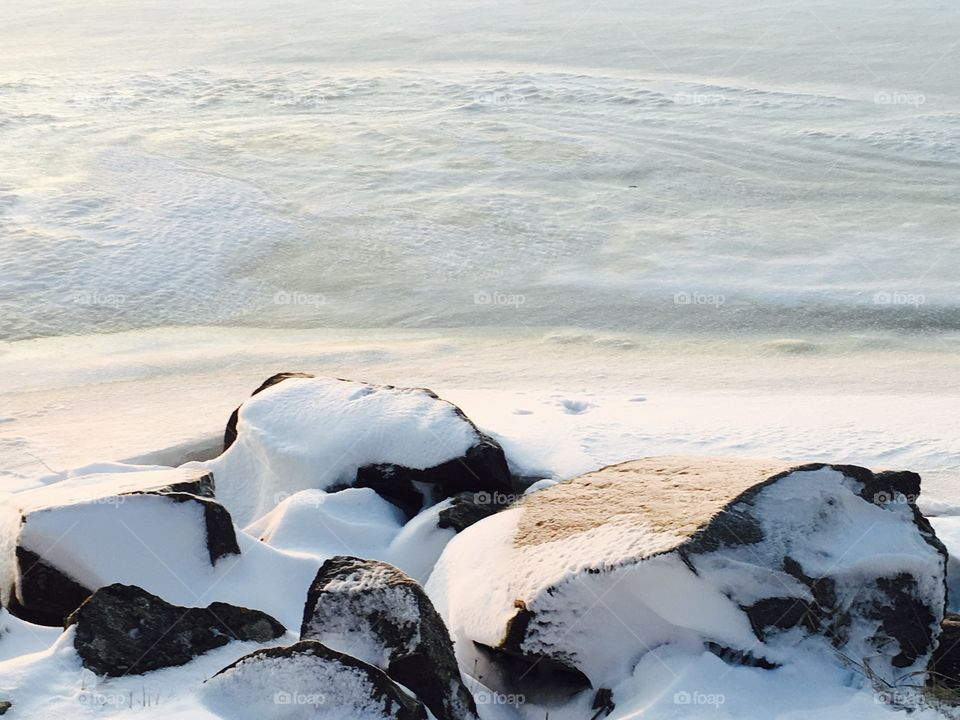 Coastline have covered with snow/ Beautiful untouched white snow on the beach stones.