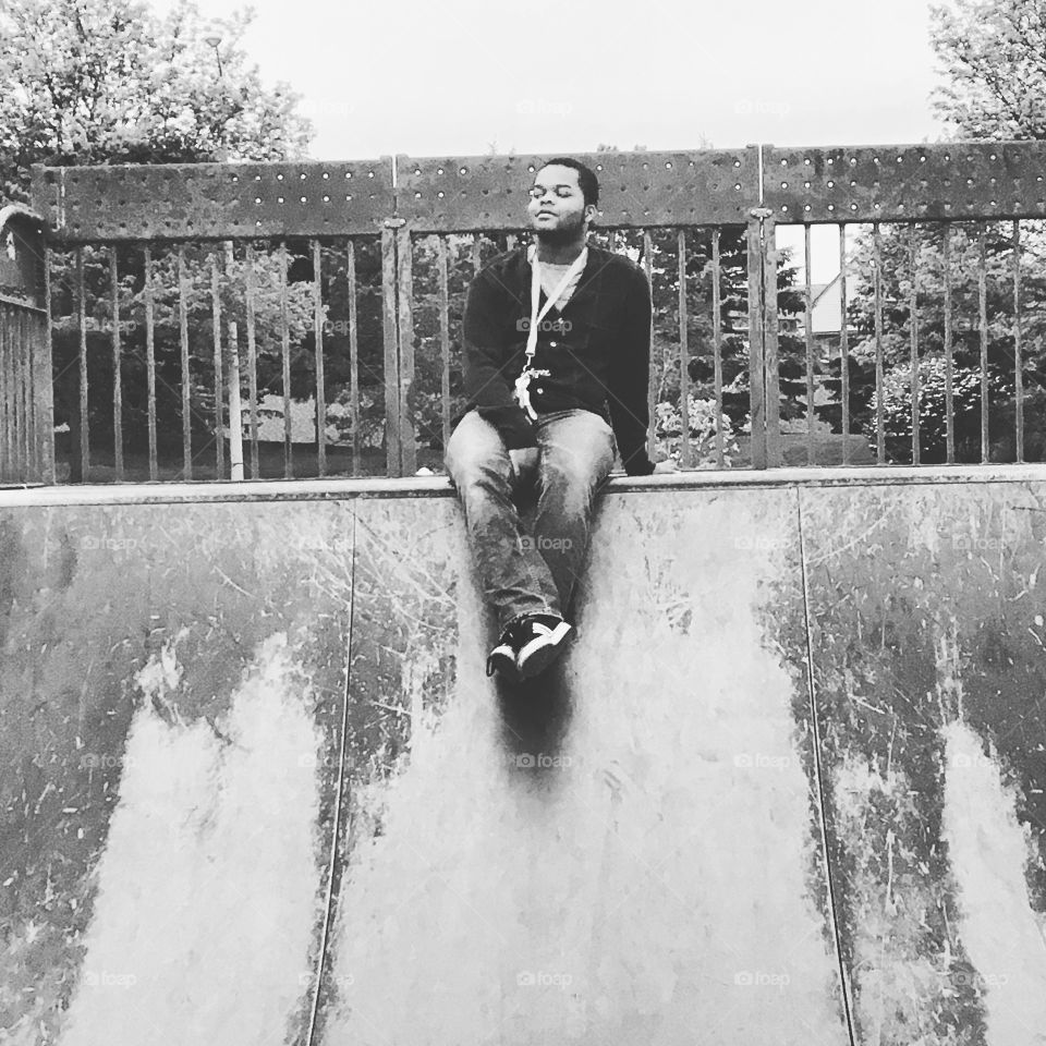 Young man sitting near railing