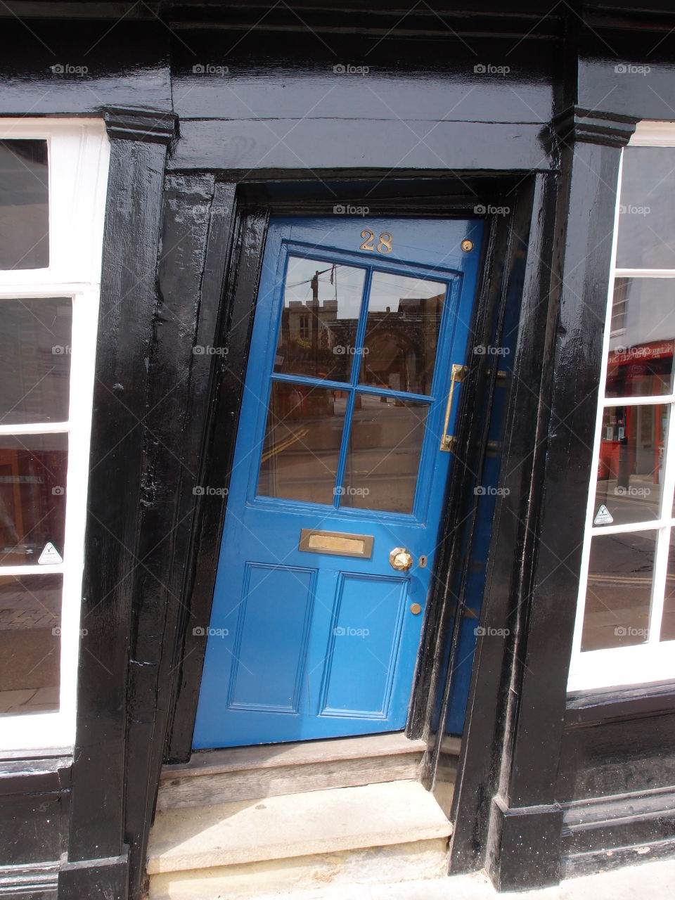 A unique slanted blue door in a black building in England on a summer day.
