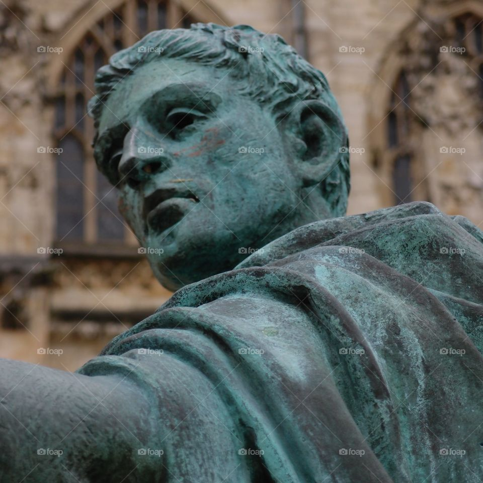 An old copper statue turned a beautiful green of a Roman figure in front of a gothic church in England.