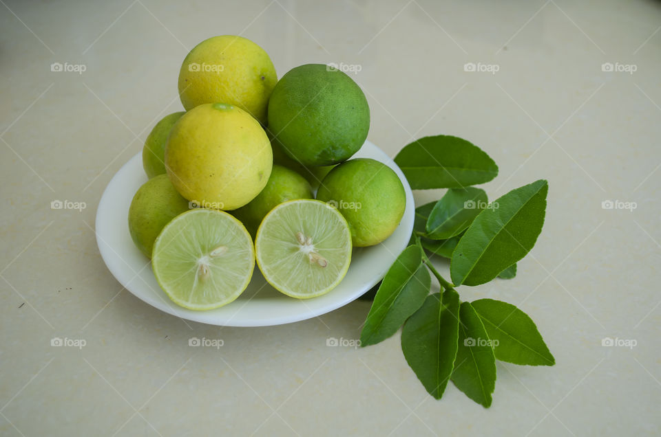 Plate on leaves is filled with yellow ripe, and green unripe limes, one of which is cut in halves