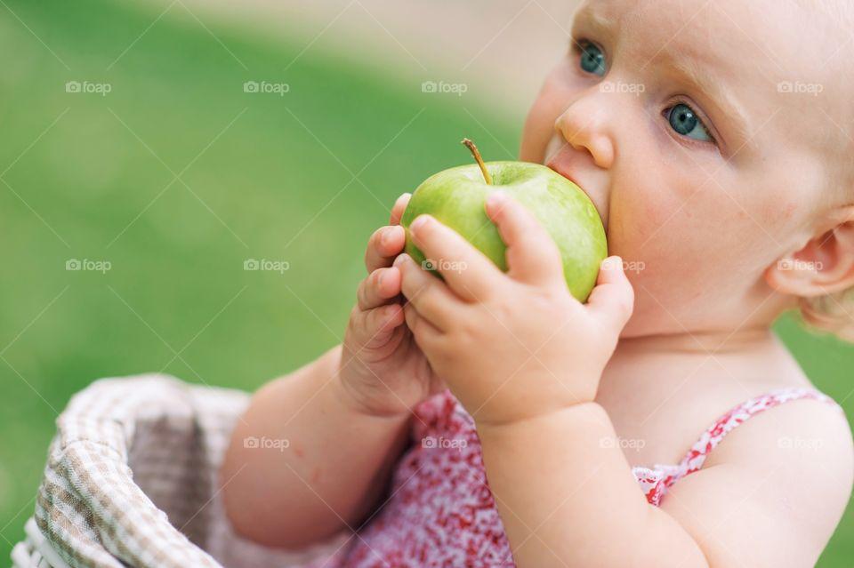 Cute little girl eating green apple