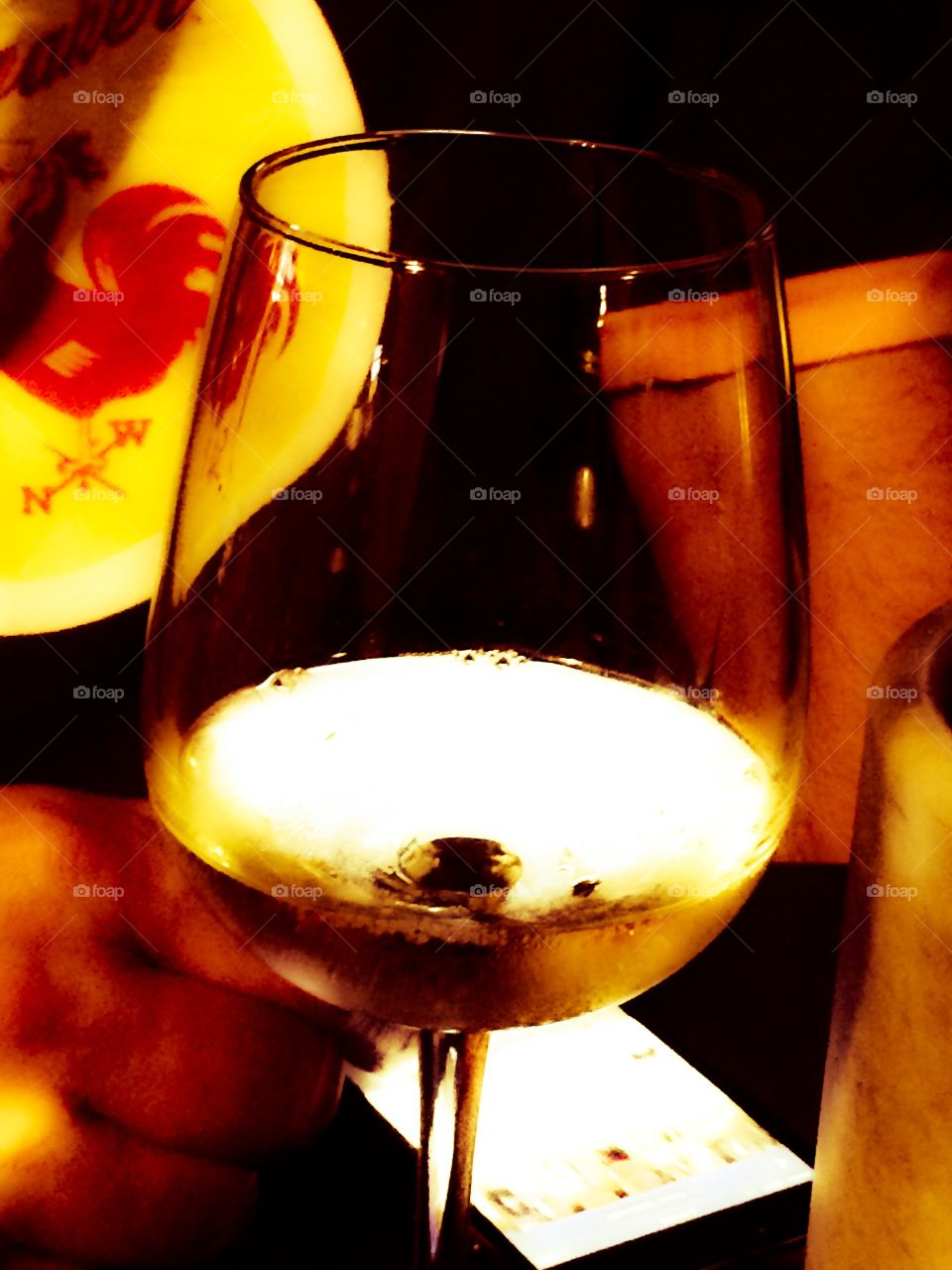 White Wine. An iPhone shines up through the wine in his glass