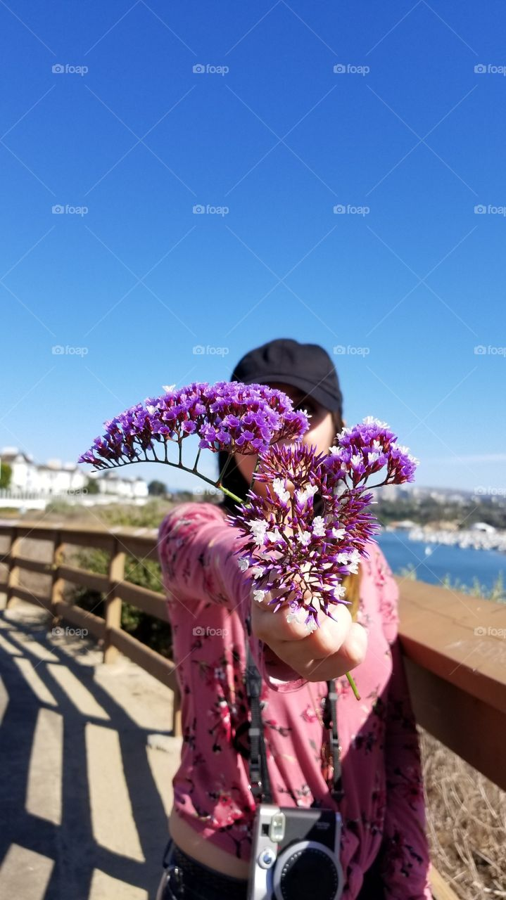 fashionable woman holding a sea lavender flower against the beautiful view of the bay and the city