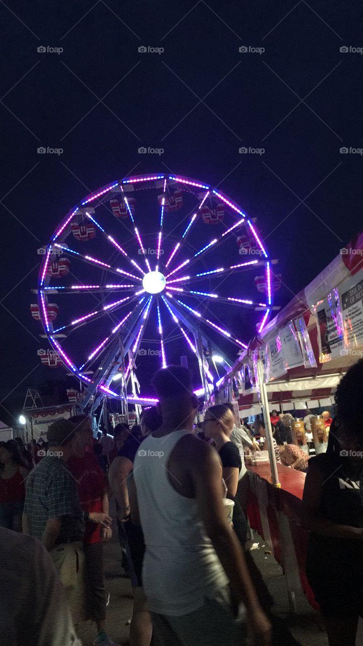 Purple Ferris wheel in a community carnival