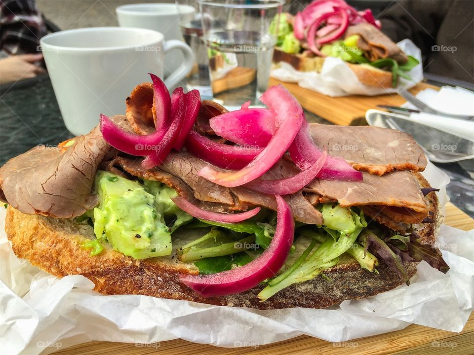 Lunch outdoors with delicious sandwich with roast beef, vegetables and pickled onion.