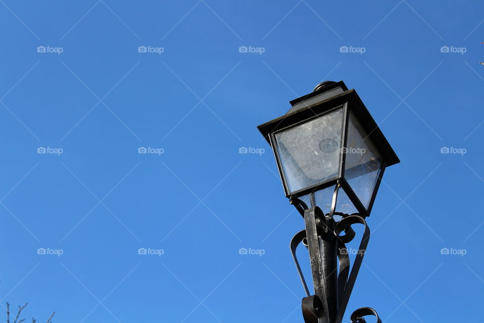 Isolated vintage lamppost on a blue sky in Autumn close-up