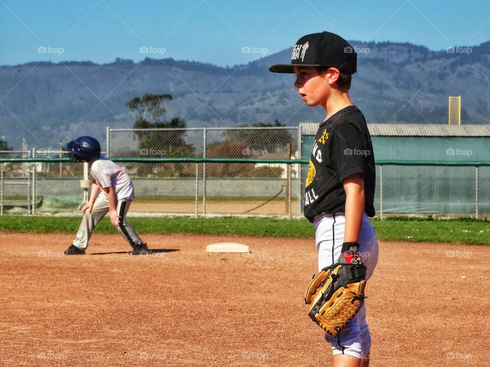 Young Boys Playing Little League Baseball. Boys Playing American Little League Baseball