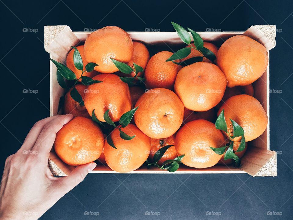 Person holding mandarin in basket