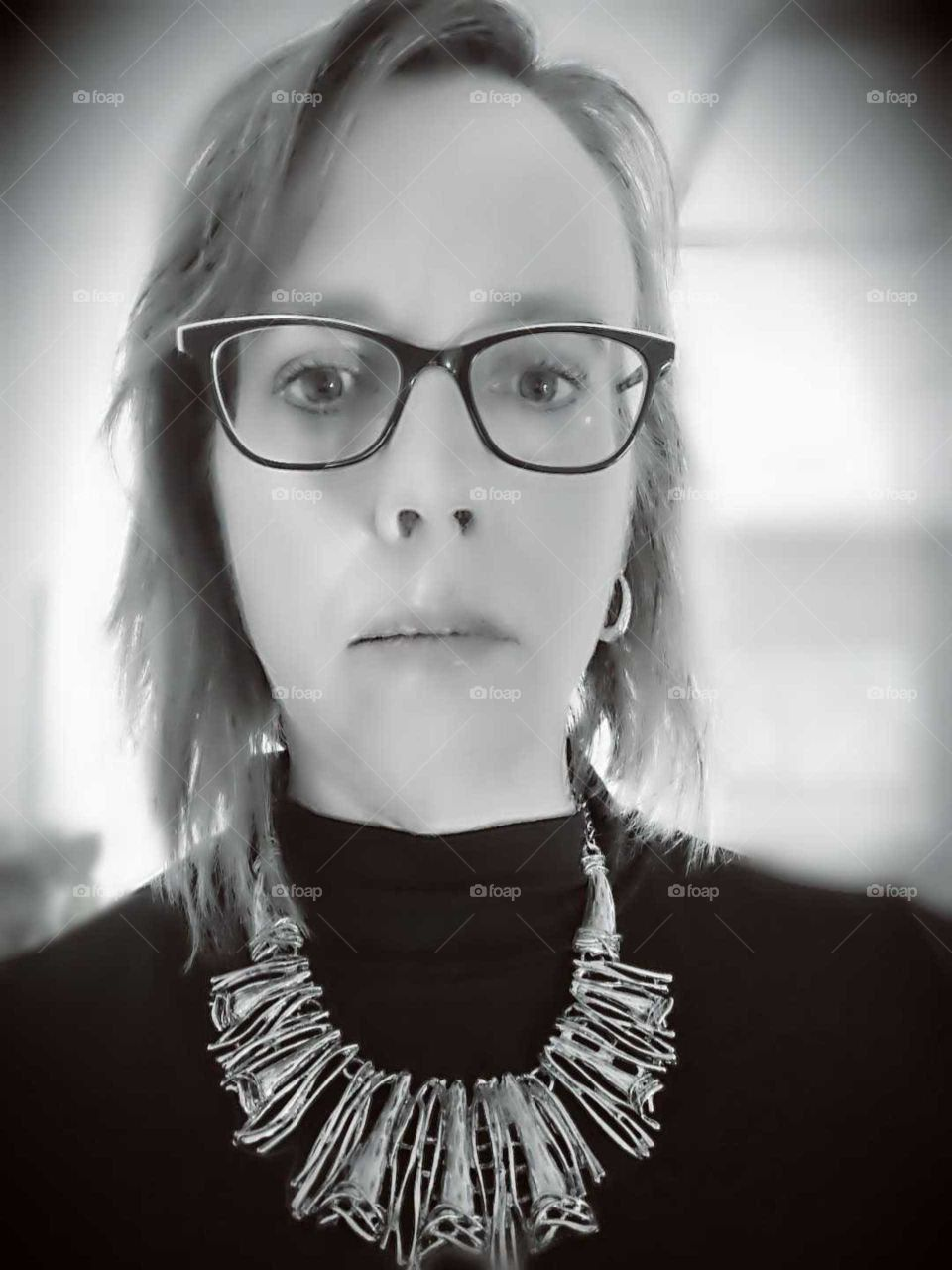 a serious woman wearing eyeglasses and a necklace