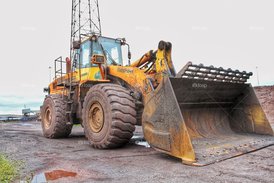 A large, JCB or digger in an industrial environment.