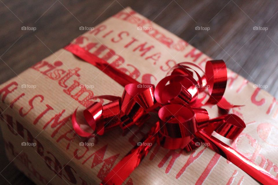 Christmas gift with red ribbon, text Merry christmas on the package