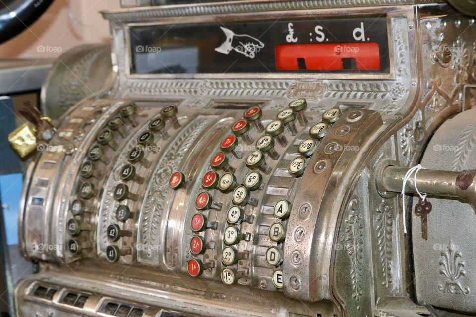 Antique steel cash register British made and currency, close up