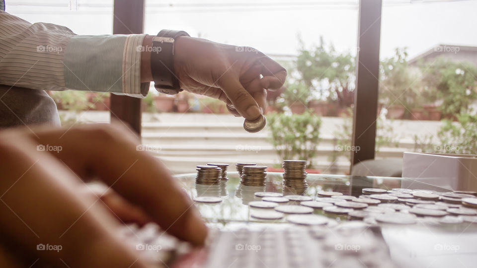 Cropped Image Of Businessman counting coins Using Calculator at Desk In Office. Businessperson Hand Counting Coins. Business Finance Savings and Investment concept. Conceptual Save money for future.