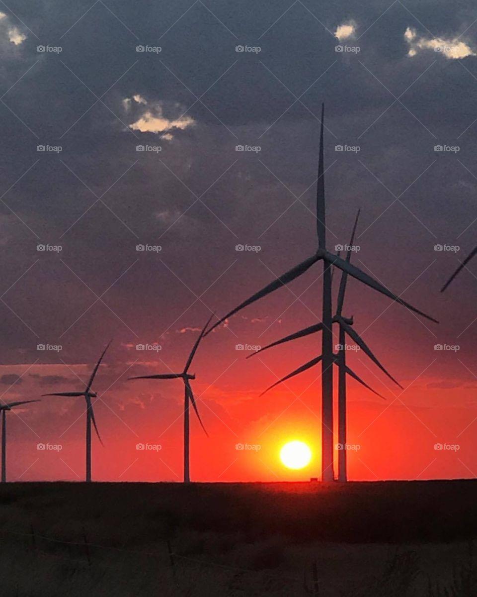 Gorgeous orange sunset sinking down behind the windmills